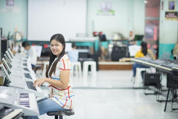 Lehrer unterrichten keyboard electone instument einem jungen im klassenzimmer