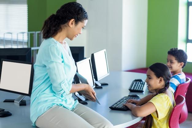 Lehrer zeigt kindern digitales tablet