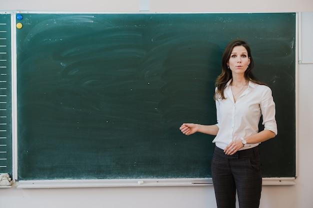 Lehrer zeigt mit dem finger auf eine leere tafel