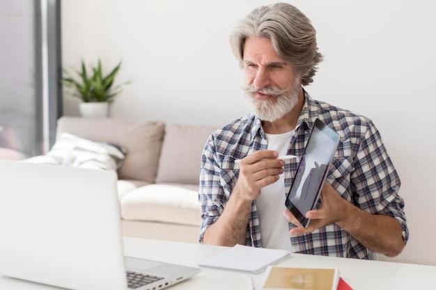 Lehrer zeigt tablette am laptop