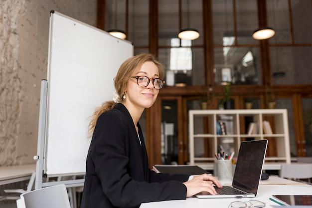 Lehrerin der seitenansicht, die am laptop arbeitet