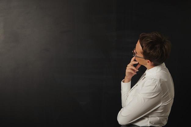 Lehrerin, die eine leere schwarze tafel betrachtet