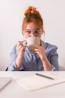 Lehrerin, die eine tasse tee während des online-unterrichts hat