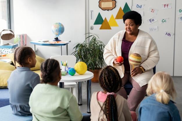 Lehrerin, die ihren schülern erklärt Premium Fotos