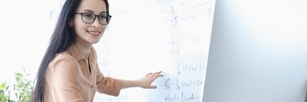 Lehrerin, die mathematische formeln auf dem computerbildschirm zeigt