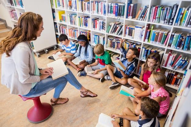 Lehrerin liest ihren schülern bücher vor