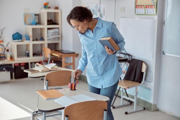 Lehrerin mit buch in einem leichten grundschulklassenraum
