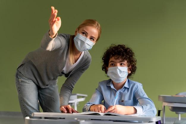 Lehrerin mit medizinischer maske, die dem jungen die lektion erklärt