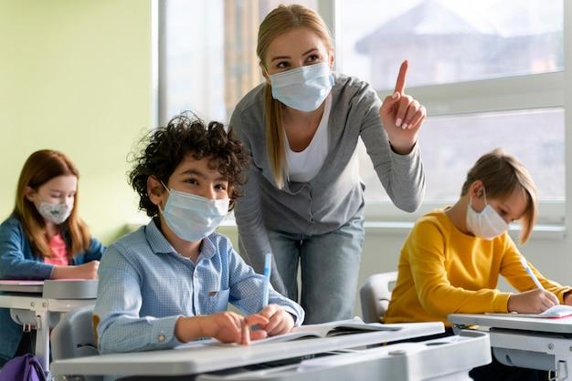 Lehrerin mit medizinischer maske, die den schülern die lektion erklärt