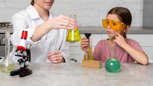 Lehrerin und mädchen machen wissenschaftliche experimente mit reagenzgläsern und mikroskop