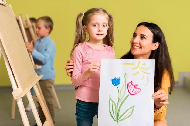 Lehrerin zeigt die schöne zeichnung ihres schülers