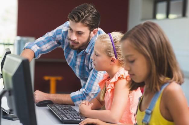 Lehrermann, der schulmädchen beim lernen des computers unterstützt