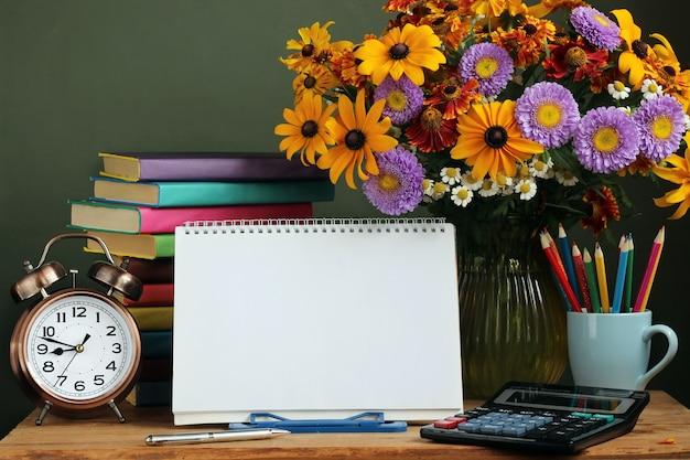 Lehrertag, 1. september. zurück zur schule. strauß herbstblumen, wecker und ein outdoor-album mit einer spirale an der basis