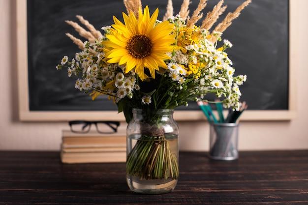 Lehrertag. schwarzes kreidebrett und frische wildblumen im vase