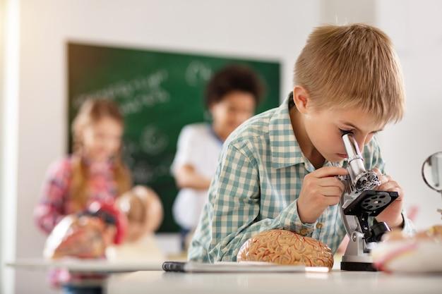 Lehrplan. netter kluger junge, der in das mikroskop schaut, während er einen biologieunterricht hat