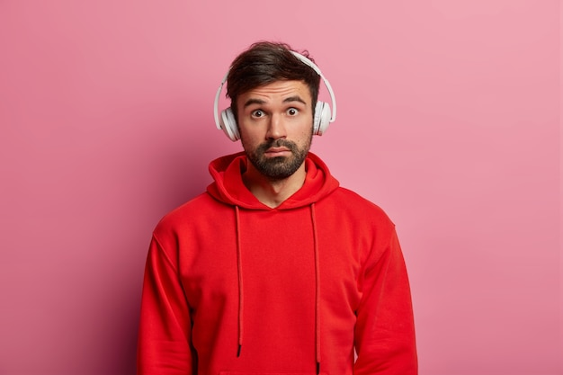 Leicht beeindruckter mann, der vor furchterregendem gesichtsausdruck betäubt ist, auf frische, erstaunliche gerüchte reagiert, audiotracks hört, roten kapuzenpulli trägt und über einer rosafarbenen pastellwand posiert. menschen, freizeitkonzept