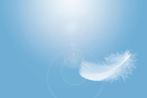 Leicht flauschig eine weiße feder, die in einem blauen himmel schwebt.