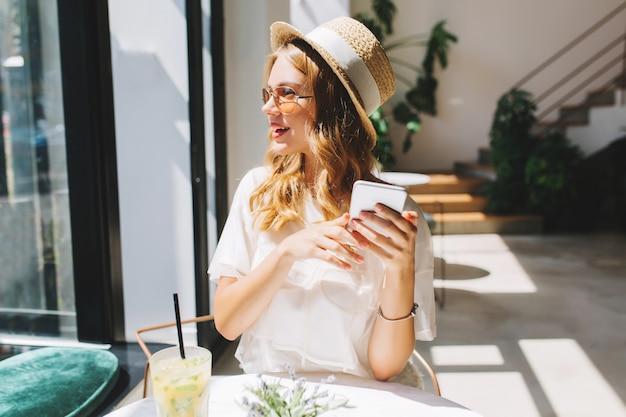 Leicht gebräuntes blondes mädchen, das mit lächeln wegschaut und smartphone in händen hält