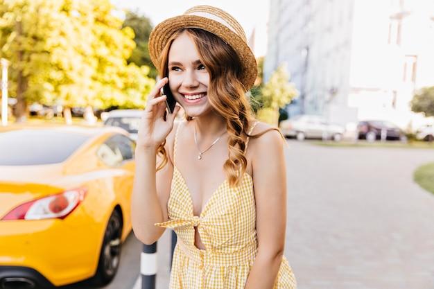 Leicht gebräuntes weibliches modell mit niedlichem lächeln, das am telefon spricht. enthusiastisches kaukasisches mädchen im gelben karierten kleid, das mit smartphone aufwirft.