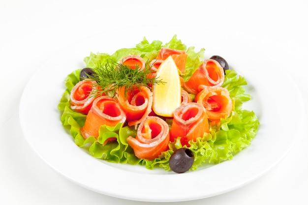 Leicht gesalzener lachs mit salat-oliven-teller auf weißem teller