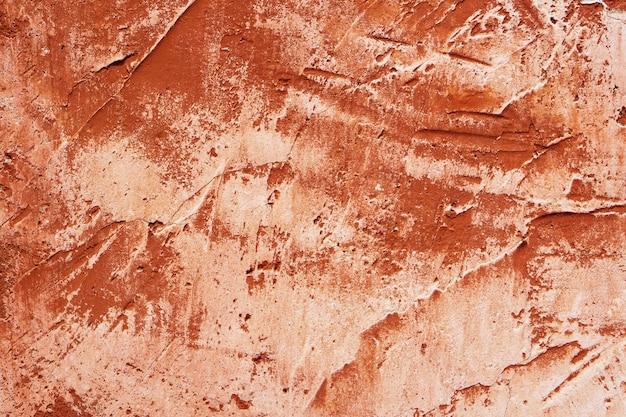 Leicht strukturierte zementwand mit gelb-orange-roter riss-peeling-farbe. grunge vintage abstrakten hintergrund.