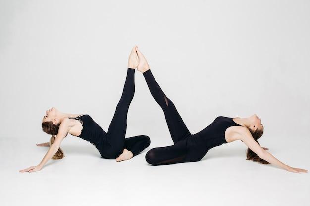 Leichtathletikmädchen, welche die yogaübung hochhält beine tun.