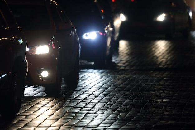 Leichte autos fahren nachts auf dem bürgersteig