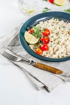 Leichte diätkost, couscous mit tomaten, limette und frischen kräutern in dunkler schale
