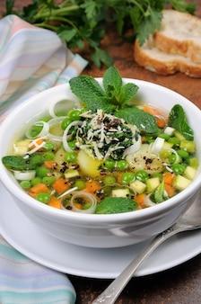 Leichte, erfrischende suppe aus karotten, zucchini, kartoffeln, lauch, erbsen, pesto, parmesan und minzblättern.