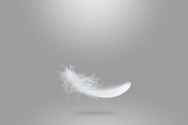 Leichte flauschige weiße feder, die in die luft fällt