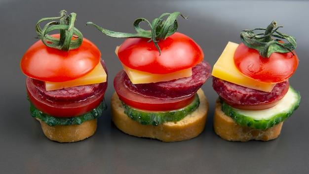 Leichte sandwiches aus gemüse, käse und würstchen