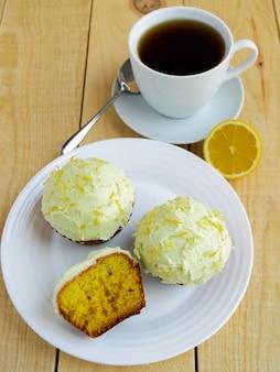 Leichte zitronen-cupcakes-muffins auf hölzernem hintergrund und eine tasse tee.