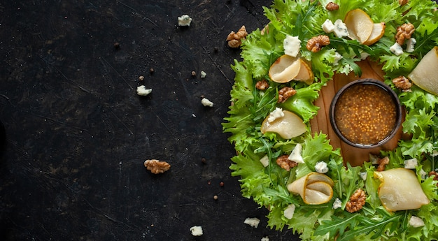 Leichter diät-salat mit birne, nüssen und blauschimmelkäse. der salat wird in form eines kranzes auf ein rundes holzbrett mit sauce in der mitte auf dunklem hintergrund gelegt. speicherplatz kopieren. hochwertiges foto