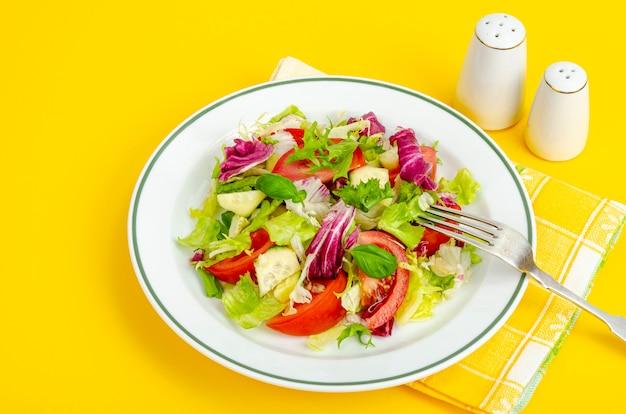Leichter diätetischer vegetarischer salat im teller auf heller oberfläche