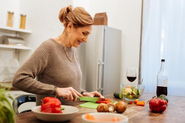 Leichter einfacher salat. angenehme aufmerksame reife dame, die minikarotten auf grünem plastikbrett hackt