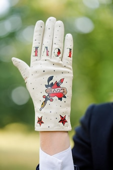 Leichter handschuh mit einem rot lackierten herzen