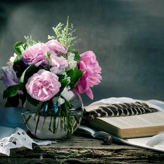 Leichter rosa rosenblumenstrauß mit alten büchern auf einem alten hölzernen.