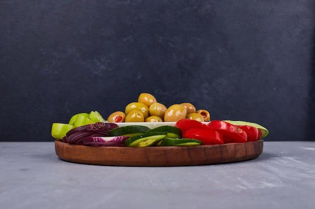 Leichter salat mit gemüse und kräutern in holzplatte.
