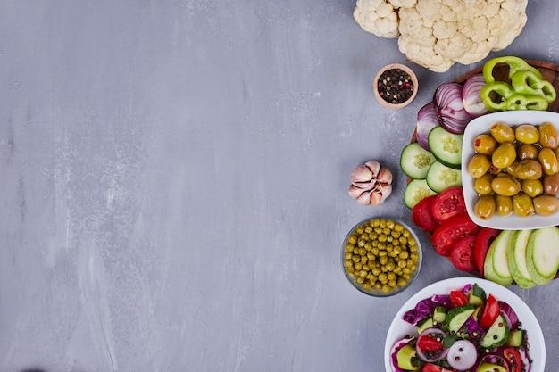 Leichter salat mit gemüse und kräutern in weißen tellern.