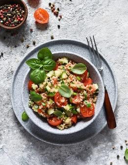 Leichter salat mit tomaten, gurken und quinoa mit olivenöl und basilikum auf einer betonoberfläche.