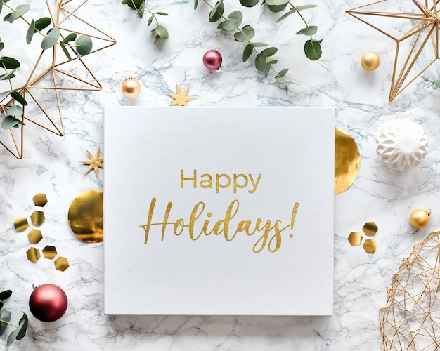 Leichter weihnachtsrahmen mit frischen eukalyptuszweigen und goldenen geometrischen verzierungen. flache lage auf weißem marmorhintergrund mit text frohe feiertage