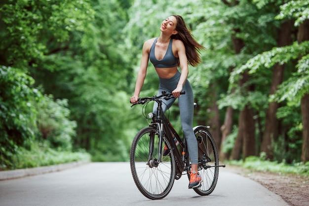 Leichter wind. weiblicher radfahrer auf einem fahrrad auf asphaltstraße im wald am tag