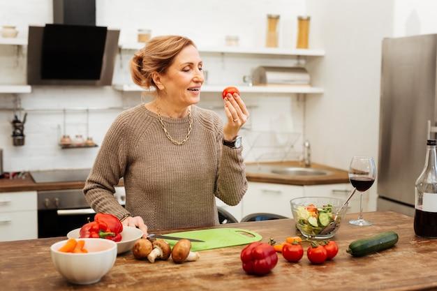 Leichtes abendessen. positive frau mit gebundenem haar, die tomate in der hand beim kochen auf holztisch beobachtet