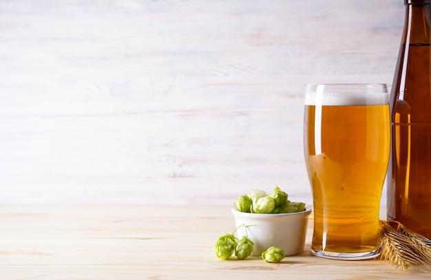 Leichtes bier und hopfen auf holzfläche, platz für text