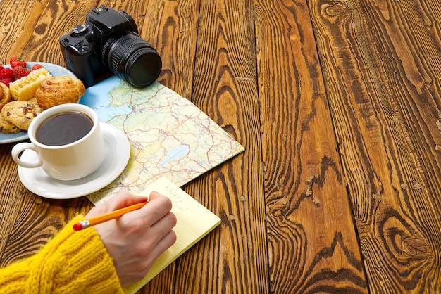 Leichtes frühstück, frisches gebäck und kaffee auf einem alten holztisch. touristisches konzept. reiseblogger-frühstück, das einen routenplan mit einer tasse kaffee erstellt