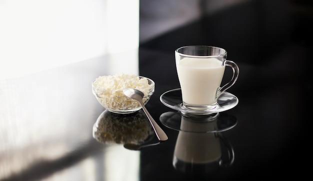 Leichtes frühstück mit milchprodukten ein glas milch und eine tasse mit hüttenkäse auf schwarzem glanz