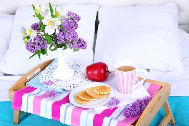 Leichtes frühstück und schöner blumenstrauß auf dem bett