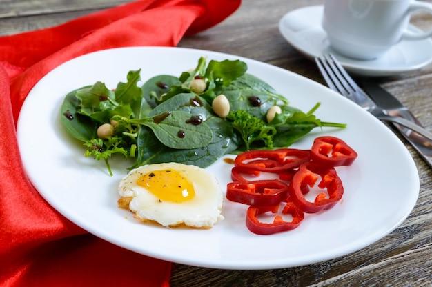 Leichtes frühstück - wachtelei, grüner salat, paprika und eine tasse tee auf einem holztisch. gesundes essen. richtige ernährung.