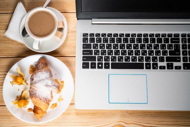 Leichtes mittagessen im büro. kaffee und croissant in der nähe der tastatur