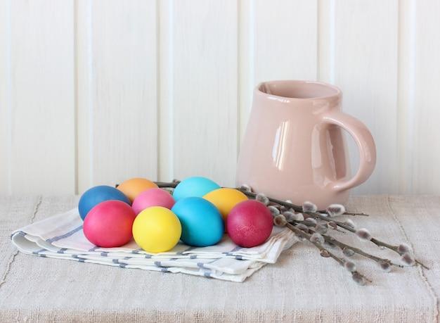Leichtes osterstillleben mit weidenzweigen und bunten eiern auf dem tisch ist eine zarte festliche komposition
